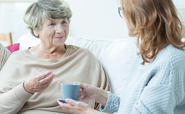 Senior woman talking to younger woman.